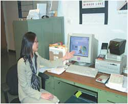 woman sitting at her desk pointing at her computer.