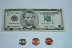 five dollar bill, dime and two pennies. 5.12 USD