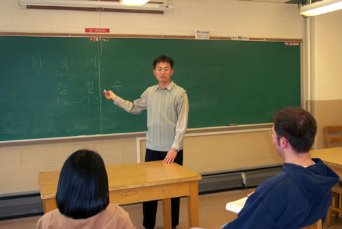 teacher Kim at the chalkboard in front of his class