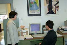 Chi-seon and Il-song talking while looking at a computer.