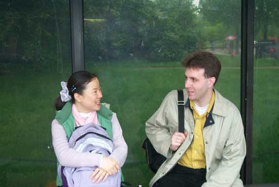 Yǒng-mi and Michael talking while sitting at a bus stop.