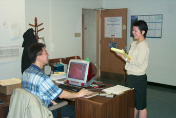 man sitting at a computer talking to a woman standing in an office