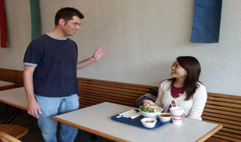 James and Sumi talking in the cafeteria