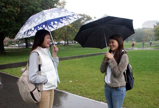 Jenny and Su-mi standing in the rain talking.